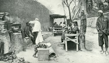 Historical Geography. 1900. Iraq. Patient customers waiting their turn in the open-air establishment of a wayside barber of Iraq.