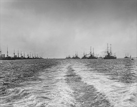 Black and white image of a wake in the ocean water from a nautical vessel and silhouetted ships