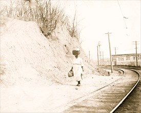 African American woman with basket on head walking near railroad tracks