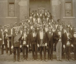 """African American men posed at entrance to building, some with derbies and top hats, and banner labeled """"Waiters Union"""" in Georgia"""