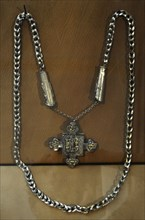 Necklace, of beads, crosses, and miniature tools.