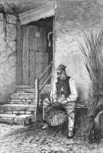 Wicker sits in front of his house and wilts a wicker basket  /  Korbflechter sitzt vor seinem Haus und flechtet einen Weidenkorb