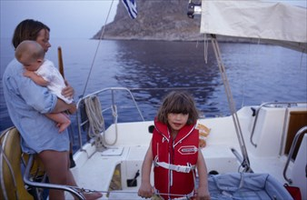 10031034 LEISURE Sailing Yachting Greece. Monemvasia. An English family on a sailing holiday aboard their yacht. Mother holding a baby near a young girl wearing a life jacket