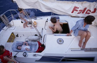 10031035 LEISURE Sailing Yachting Greece. View over a family on a sailing holiday aboard their yacht. Mother with children and a baby lying in a carry cot