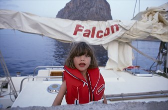 10045186 CHILDREN Leisure Yachting Greece. Monemvasia. An English family on a sailing holiday aboard their yacht with a young girl wearing a life jacket