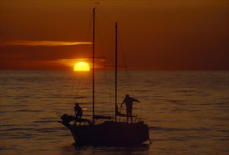 10045658 LEISURE Sailing Yachting Two people seen on a sailing boat at sunset with red sky and a low sun. Borth  Wales  UK