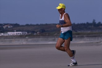 10001965 SPORT  Jogging Jersey . St Ouens Bay. Elderly man jogging on sandy beach