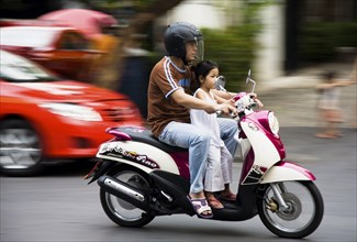Father with young daughter on motorcycle pass brightly coloured taxis.