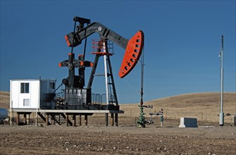 Canada, Alberta, Milk River Ridge , Oil pump jack or nodding donkey on the edge of the Baaken play  Flare tower at right.